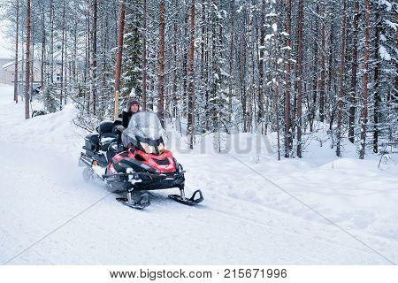 Rovaniemi Finland - March 3 2017: Woman riding red snowmobile in winter forest in Rovaniemi Lapland in Finland