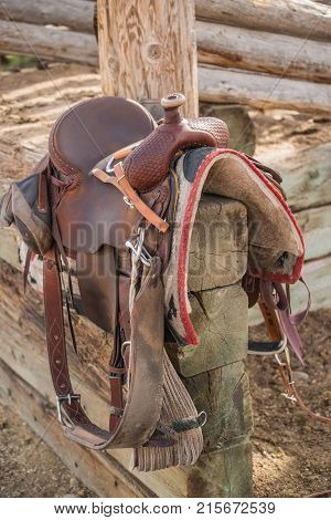 Western riding saddle and horse blanket on wooden corral post after a trail ride