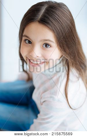 Irresistible smile. Top view of sweet cute little girl who sitting and gazing at the camera while smiling happily