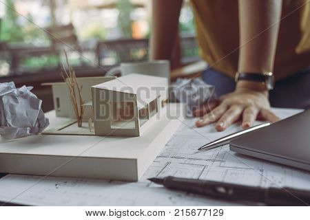 Closeup image of a stressed architects thinking and drawing shop drawing paper with architecture model and laptop on table while fail