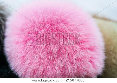 Pink natural fur pompon texture. Selective focus