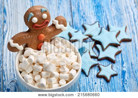 Blue glass mug with hot cocoa and marshmallows, homemade gingerbread man, handmade ginger cookies on a blue wooden background. Christmas and New Year background.