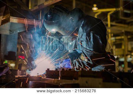 welder is welding assembly car part in factory