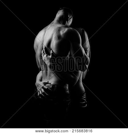 Heterosexual couple with shirtless man and woman in black dress hugging on black background. Black and white