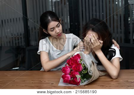 Stressed frustrated young Asian woman supporting depressed crying female friend in living room. Break up or best relationship concept.