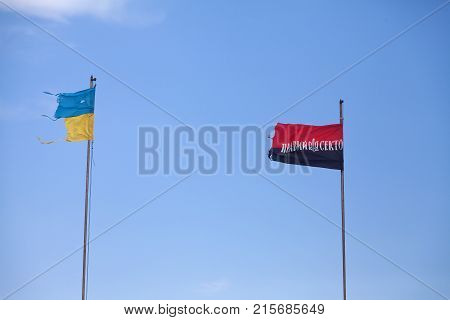 Ukrainian damaged flag and flag of Arms of Ukrainian Nationalists (OUN-UPA) against blue sky