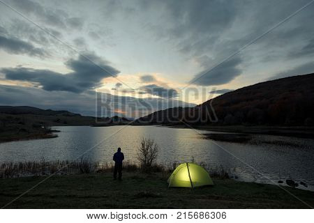 man and his lighting tent against sunrise on the Biviere Lake in Nebrodi Park, Sicily