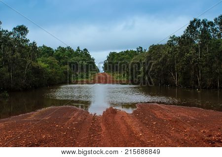 flood water over an unmade gravel road