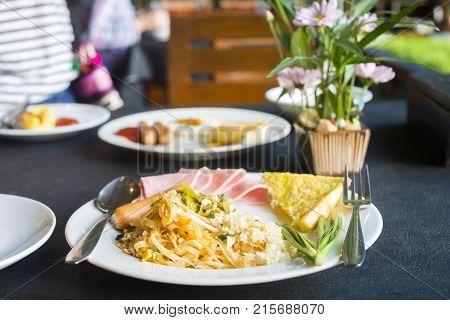 Breakfast set (Pad-Thai Koa-pad) on table in the restaurant. Thai food.