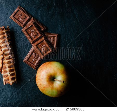Chocolate, waffer tube and apple on the black board