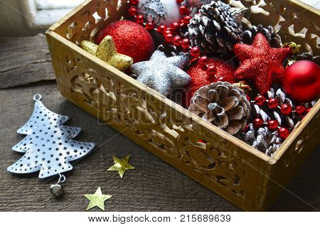 Christmas tree decoration: red and silver shiny balls,stars and pine cones in a vintage wooden box.Prepare for Christmas Eve or New Year winter holidays.Selective focus.