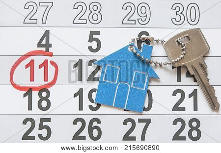 House key on a house shaped keychain resting on calendar background. Concept for real estate, moving home or renting property