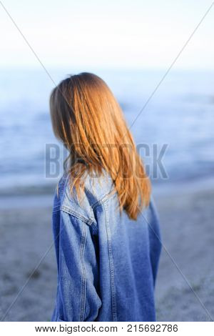 Joyful woman rests from bustle of city, standing with back to camera on shore of endless sea. Young woman rejoices, raises hands up and with smile on face laughs with happiness, develops hair and wags head, standing on background of sea and blue sky on wa