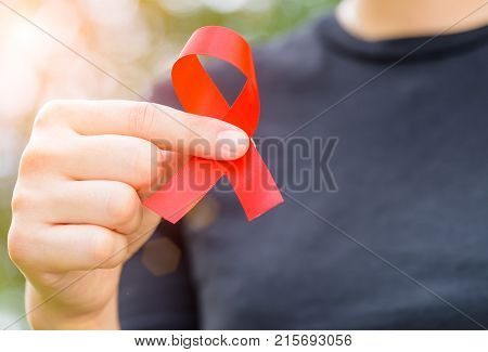 World Aids Awareness concept. Woman hands holding red AIDS awareness ribbon.