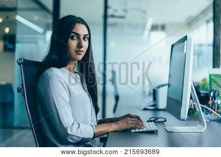 Portrait of confident young Latin-American businesswoman wearing white shirt sitting at table in office, working on computer and looking at camera