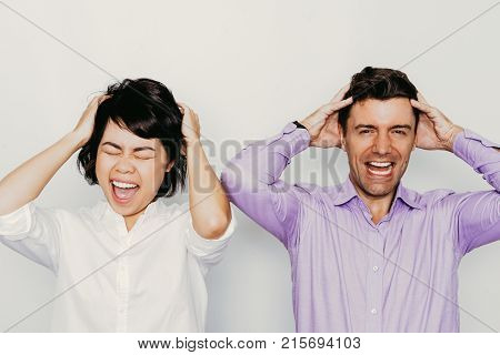 Portrait of two stressed colleagues, Caucasian businessman and Asian businesswoman, standing holding head in hands, looking at camera and screaming