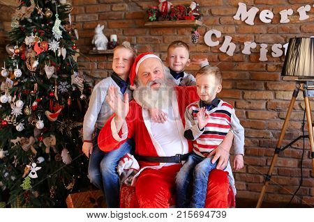 Happy male children and Christmas grandfather posing smiling at camera. boys cheerfully wiggle their hands Santa Claus shows gesture with thumb up, sitting in comfortable armchair, cozy large room, decorated Christmas, fashionable floor lamp, walls on whi