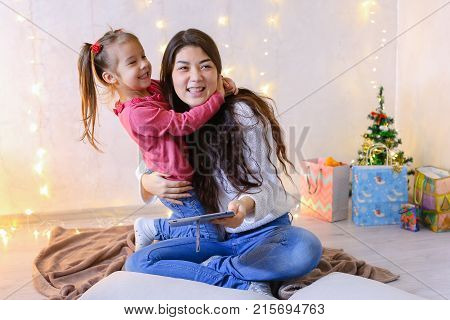 Beautiful girl and elder sister of small female child cares for younger sister and talks, fools around and laughs cute in family way, sitting on floor in bright room against backdrop of glowing garland and small festive tree on eve of new year. Woman with