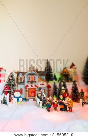 kid gospel choir singing and reads bible in the middle of Christmas village. Winter fairytale miniature scenery