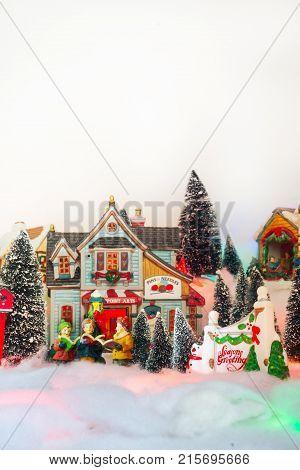 kid gospel choir singing next to Seasons greeting in white Christmas village. Fairytale miniature scenery