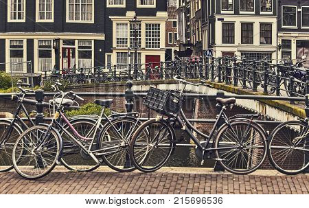 Bike over canal Amsterdam city. Picturesque town landscape in Netherlands.