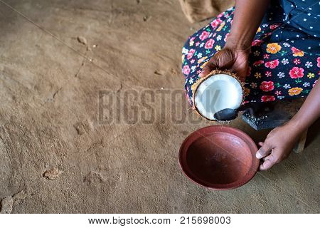 Close up woman in traditional Indian clothing holding grater for coconut to make copra