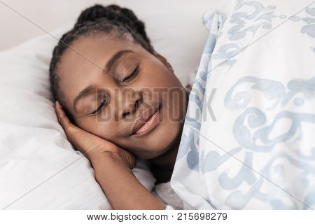 Content young African woman fast asleep under the duvet of her bed at home in the early morning