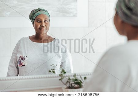 Stylishly dressed young African woman wearing a headscarf standing in her house looking at her reflection in a mirror