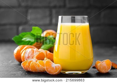 Tangerines peeled tangerines and tangerine juice in glass. Mandarine juice and fresh fruits with leaves.