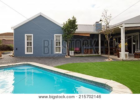 Exterior of the swimming pool and landscaped backyard of a contemporary suburban home