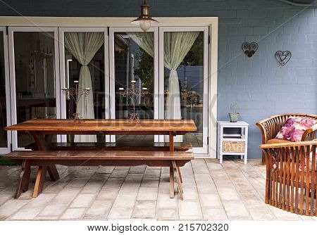 Exterior of a picnic table on a patio in the backyard of a contemporary suburban home