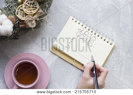 A hand writing 2018 goals in notebook, pink tea cup with saucer, christmas wreath with natural decorations on a light concrete background, top view