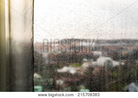 Looking Through A Window With Curtains And Raindrops On The Window