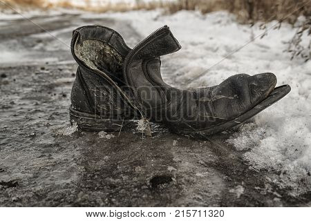 Old shoe. Grunge shoe. Grunge background. Boots on the snow. Old shoes. Shoe. Grunge boot. Worn boot.