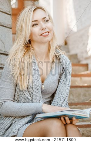Young elegant woman sitting on stairs outside enjoys a book reading