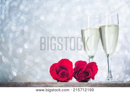 Champagne and red roses on wooden background