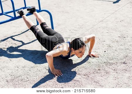 sportive teen in a bright blue sport bra and black leggings doing push ups on the sport playground. Photo of an athlete girl with a beautiful sports body