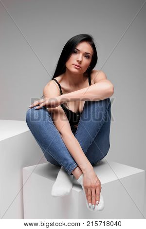 attractive young teen in black brassiere and jeans sitting in lotus pose on cube in studio on gray background