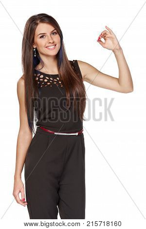 Smiling elegant business woman in black holding imaginary sewing in her fingers, over white background