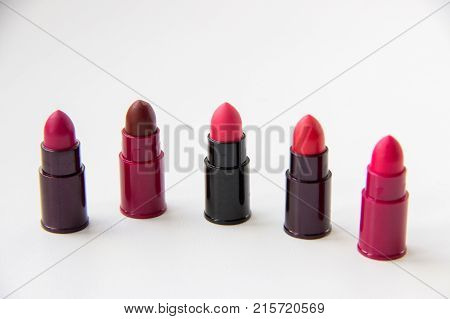 Several probes of lipsticks with red hues on a white background