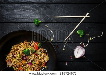 Udon Stir Fry Noodles With Chicken And Vegetables In Wok Pan On Black Wooden Background With Chopsti
