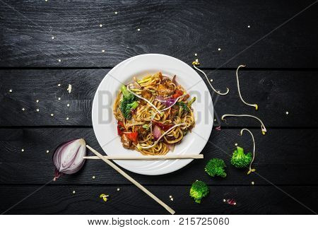 Wok. Udon Stir Fry Noodles With Chicken And Vegetables In A White Plate On Black Wooden Background.