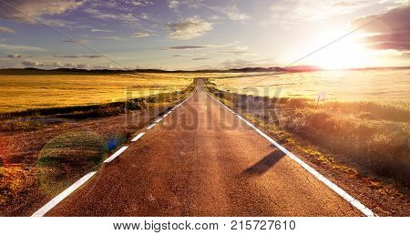 Adventures and road trips.Sunset and travel concept.Road and fields