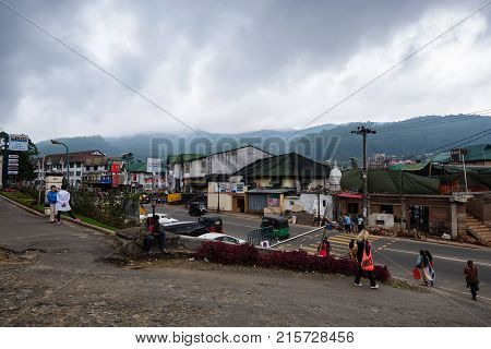 NUWARA ELIYA, SRI LANKA - DECEMBER 2012: Picture of road, cars and houses on city street on cloudy day