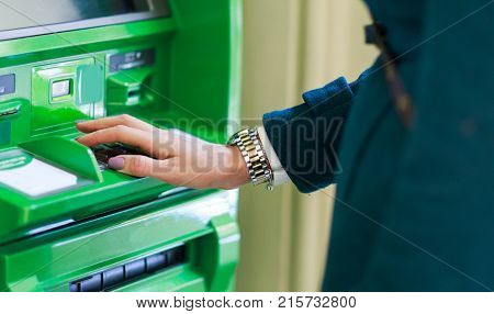 Image of woman in coat at green cash machine in room