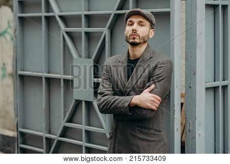 Handsome Confident Mature Man With Beard Stands On Wooden Brown Background With Copy Space For Your