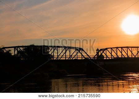 silhouette railway bridge and reflex in river before sunrise in the morning with copy space add text