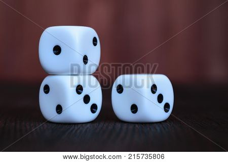 Stack of three white plastic dices on brown wooden board background. Six sides cube with black dots. Numbers 1 2 and 3.