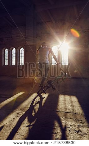 BMX stunts in a sunray indoor gothic hall.