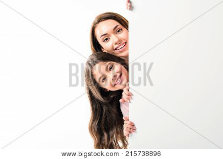 Mother and daughter looking out from empty board isolated on white